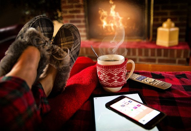 Cozy image of feet in fuzzy plaid slippers, warm drink, fireplace