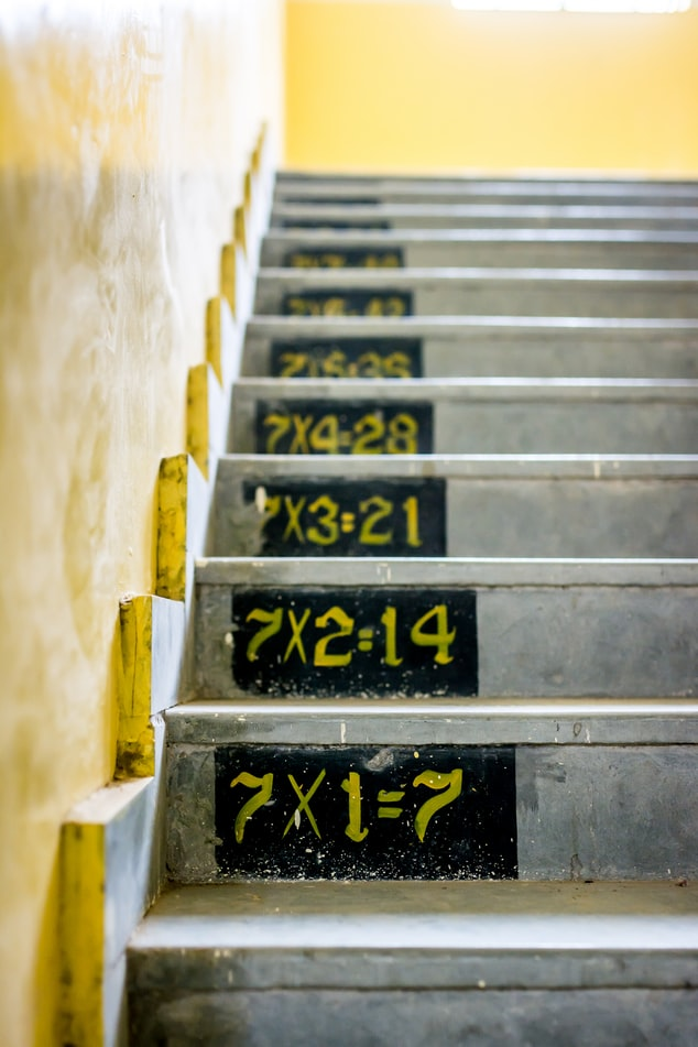 cement steps painted with multiplication tables for multiples of seven 7X1=7, 7X2=14, etc.