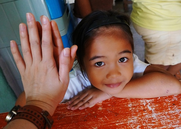 adult hand high-five with small child looking up at the camera.