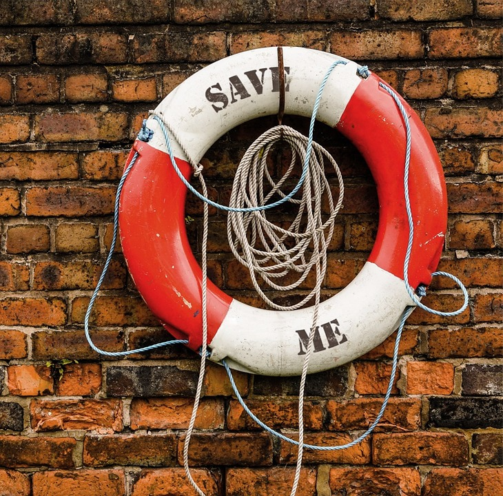 red and white rescue life ring hanging on a brick wall letters SAVE ME.
