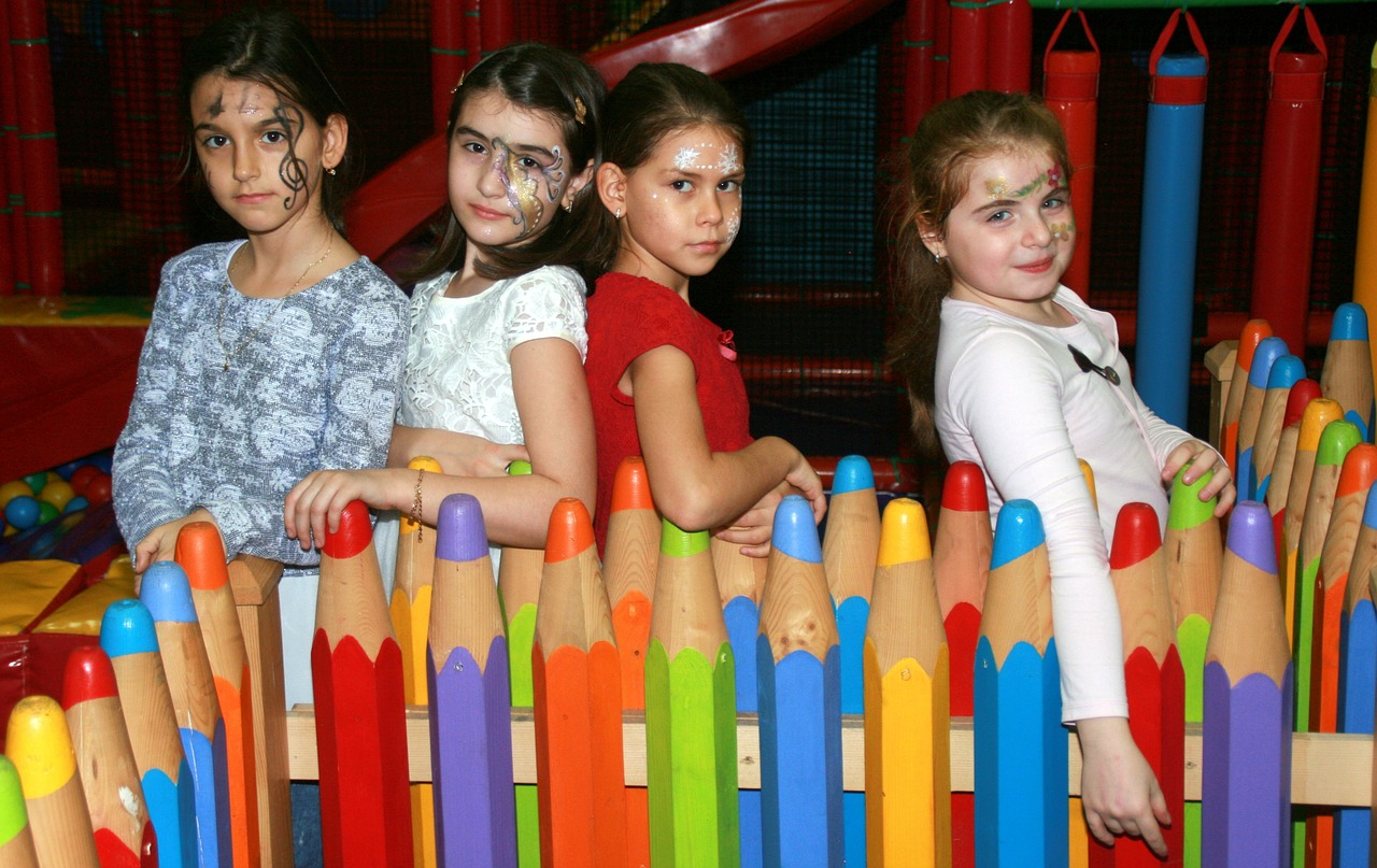 kids leaning on colored pencil fence