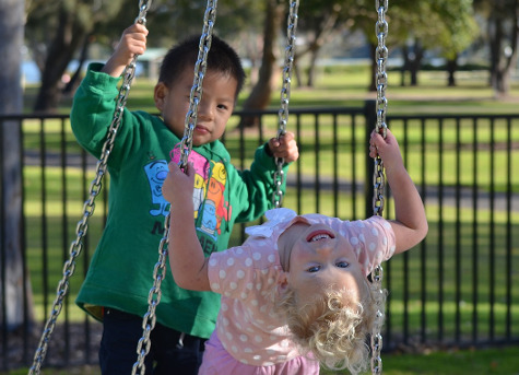 two children playing on swing-set at park