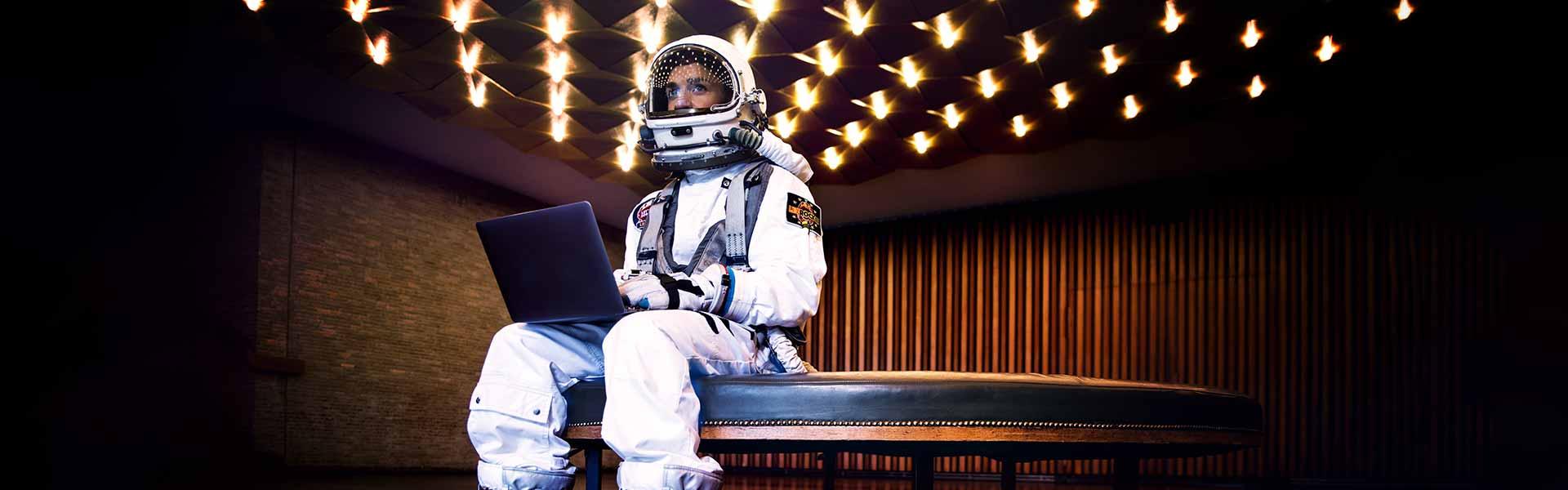 Sitzender Astronaut mit Laptop auf dem Schoß