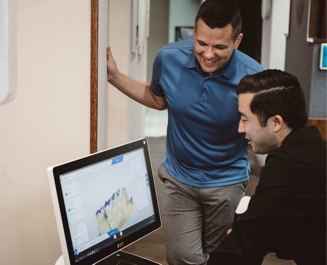 Photo of Dr. Kyle and a patient looking at a 3D dental image on a computer