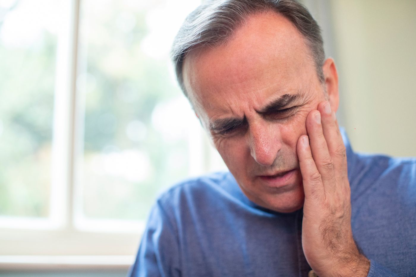 a older man wincing in pain and holding his jaw