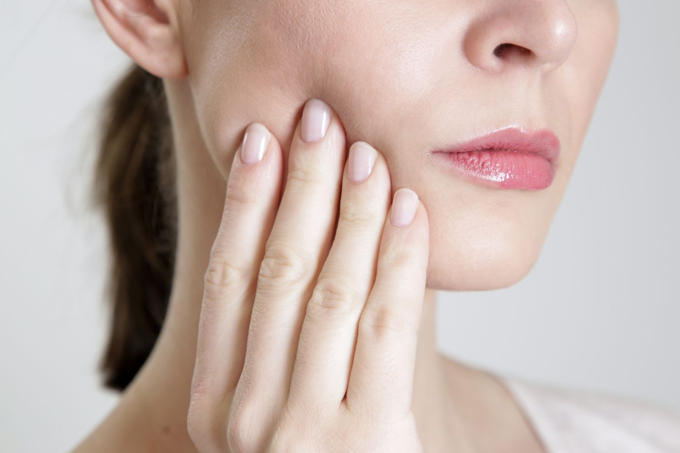 Woman touching her jaw because her tooth hurts