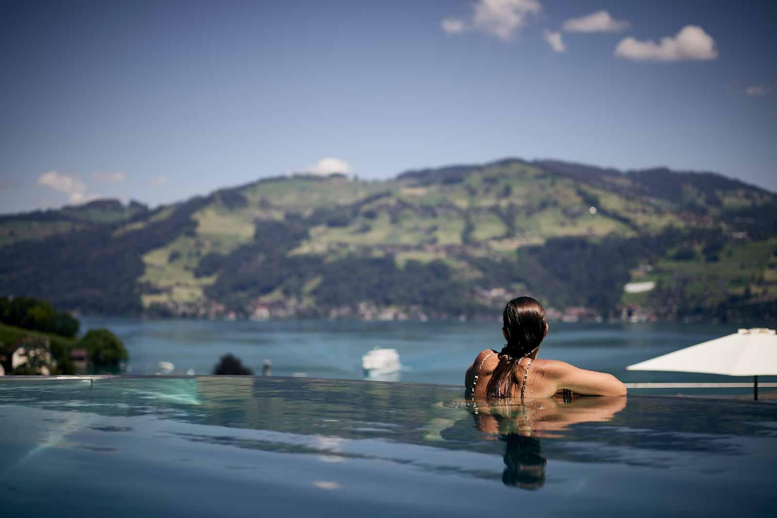 Frau in Infinity Pool mit Sicht auf den Thunersee