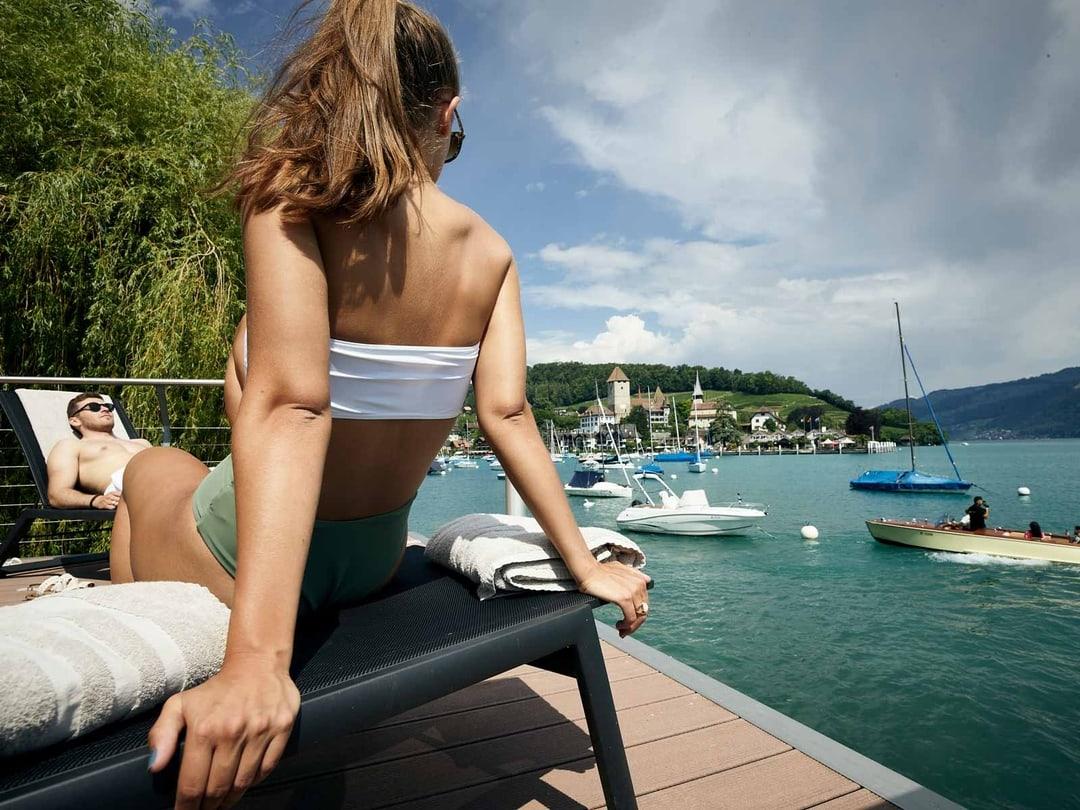Frau sitzt auf Liegestuhl im Strandbad