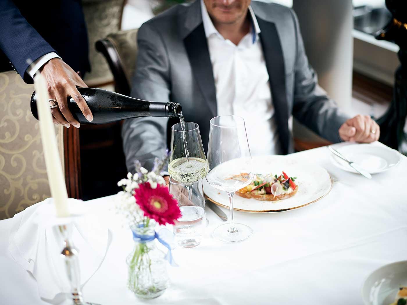 Weinglas wird mit Weisswein aufgefüllt