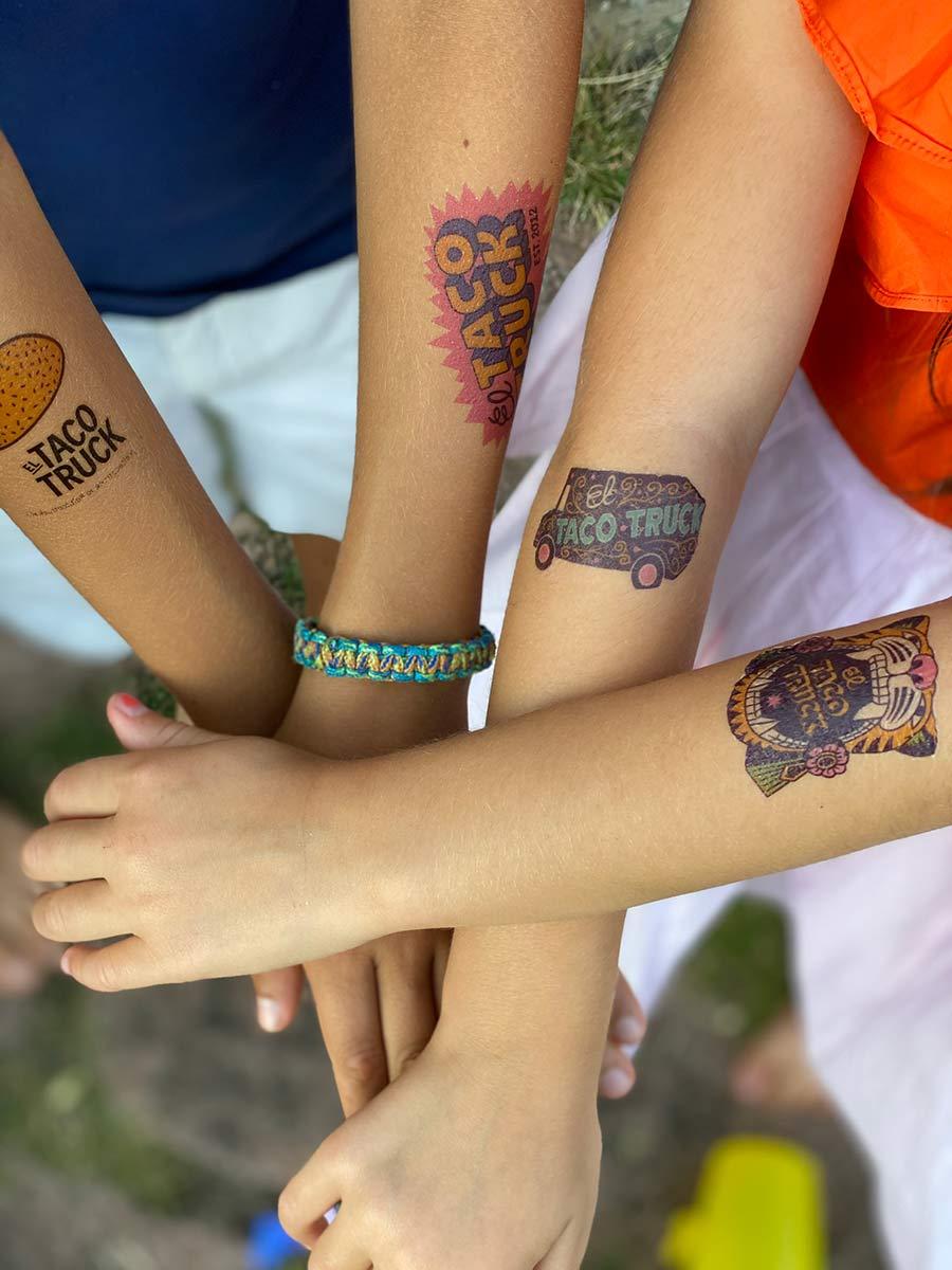 Armar med temporära tatueringar från el taco truck