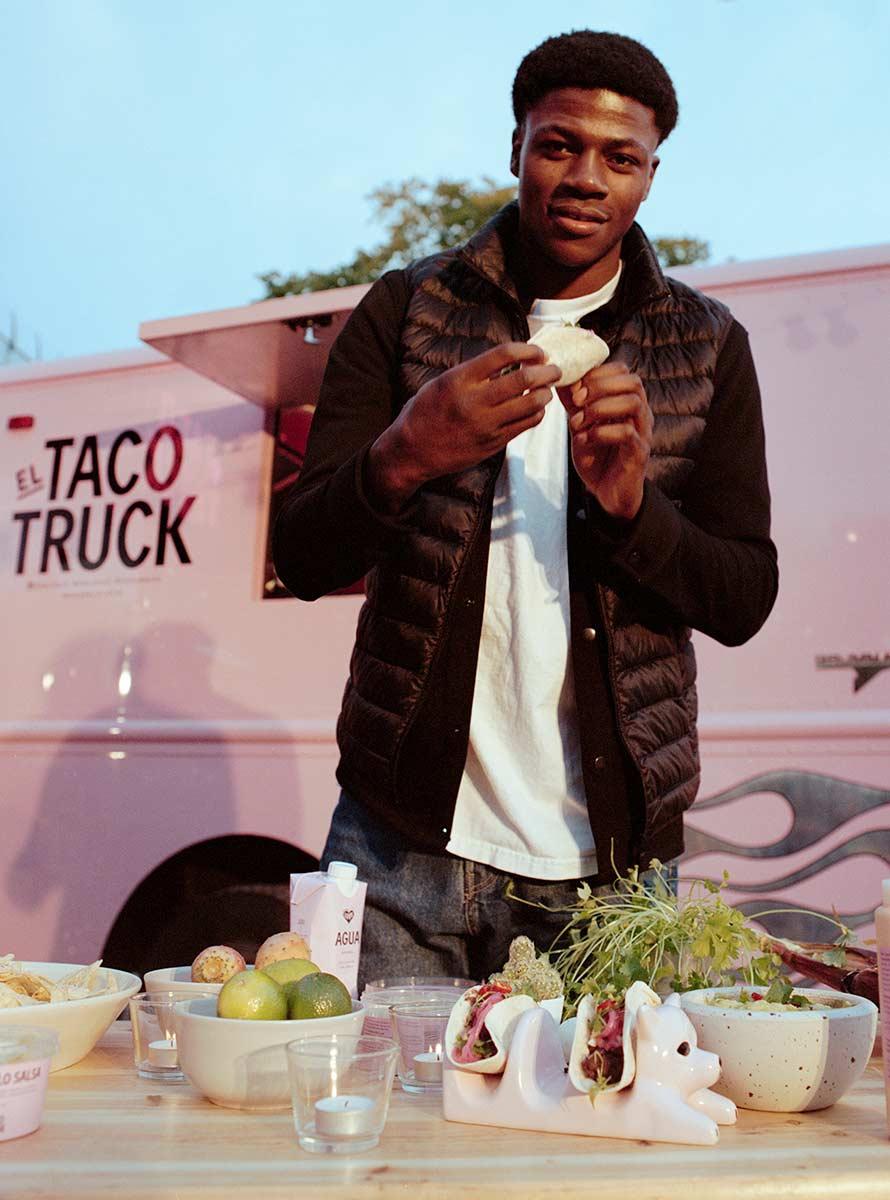 Person som står vid ett bord med tacos framför El Taco Trucks foodtruck