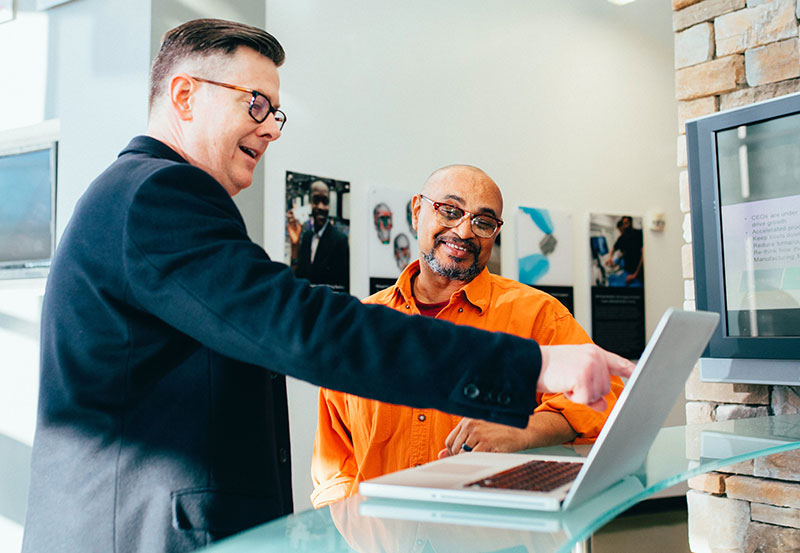 An IT consultant talking to a sales manager about software on a laptop