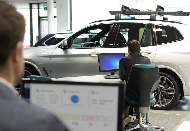 Two sales managers using computers in a car showroom