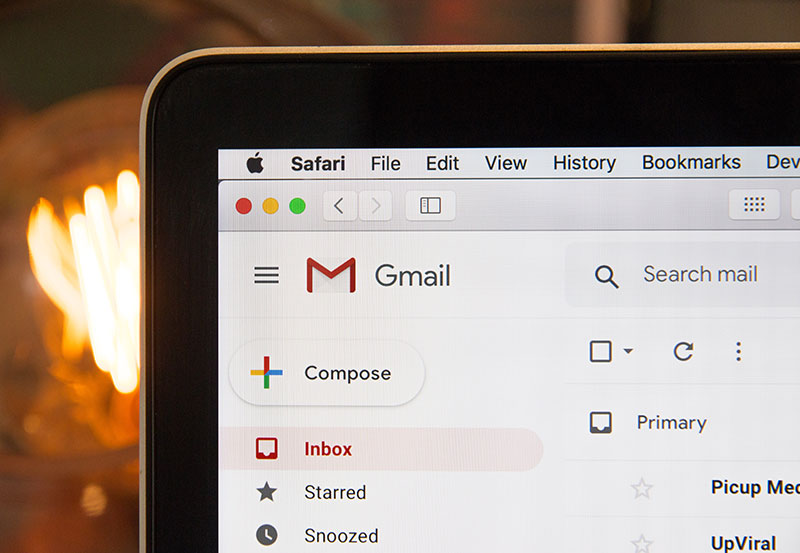 A Gmail inbox displayed on the corner of a laptop screen