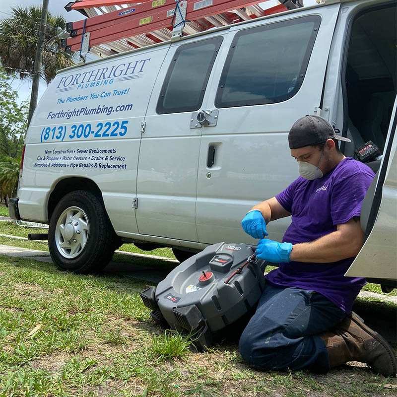 Owner of Forthright Plumbing checking drain clearing equipment in front of company van in Tampa, FL