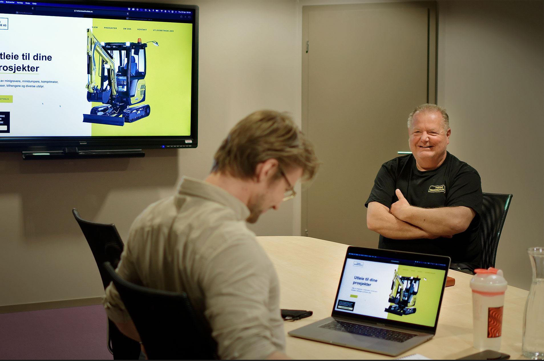 To personer i godt humør som sitter på hver sin side av et bord, og diskuterer design av nettside