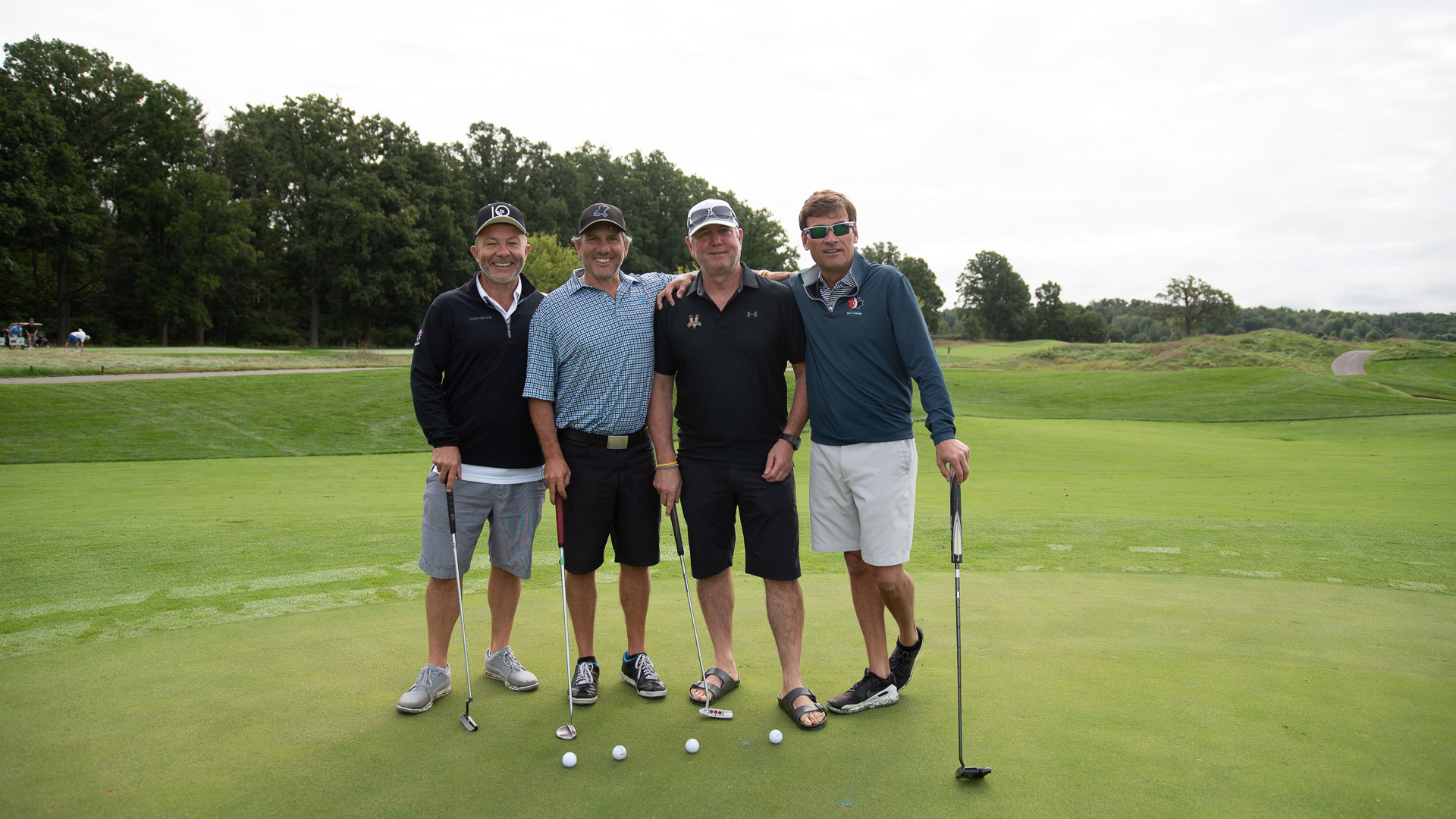Group of four men standing on golf course with clubs, smiling
