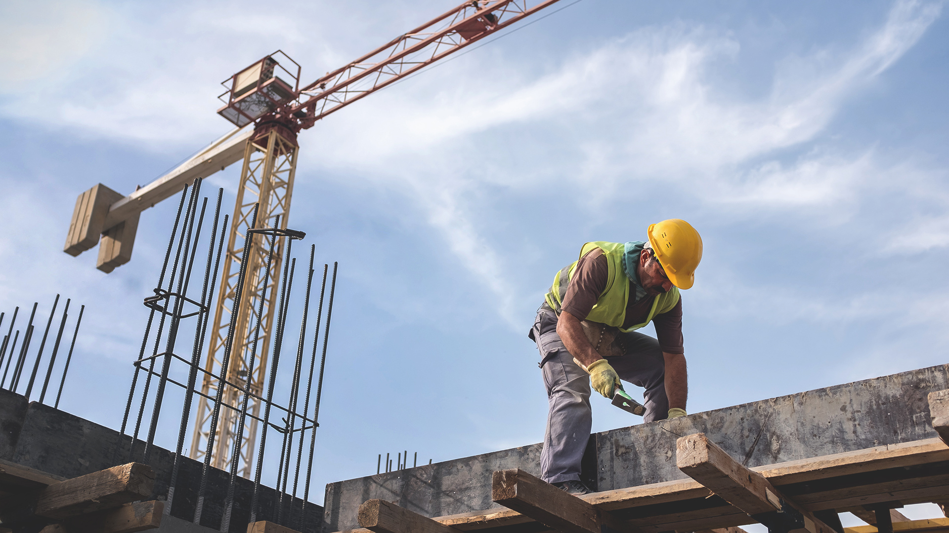 Construction worker in hard hat bent over concrete beams, with crane and blue sky in background