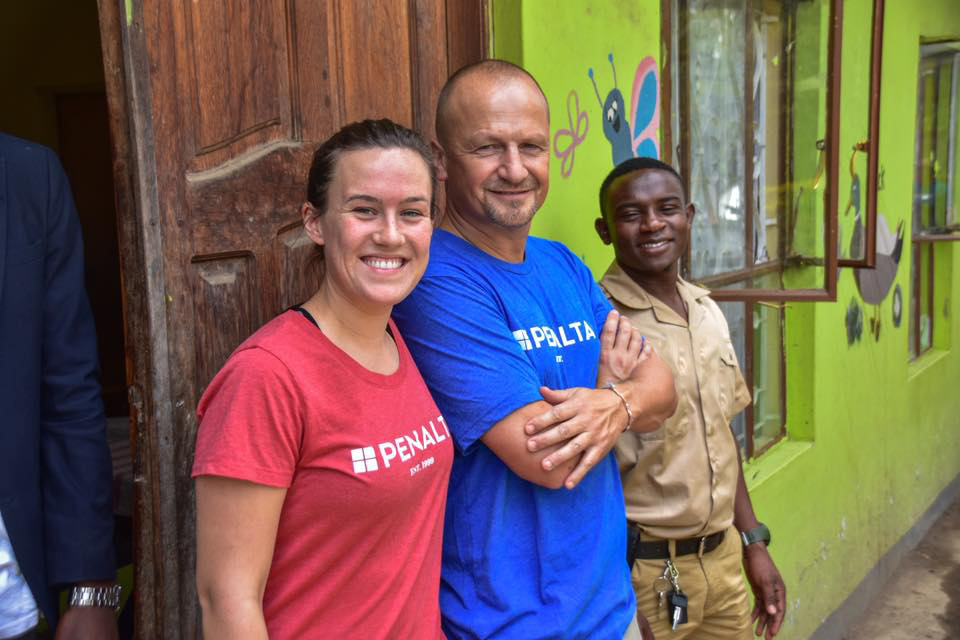 Three people smiling, leaning against outside of building