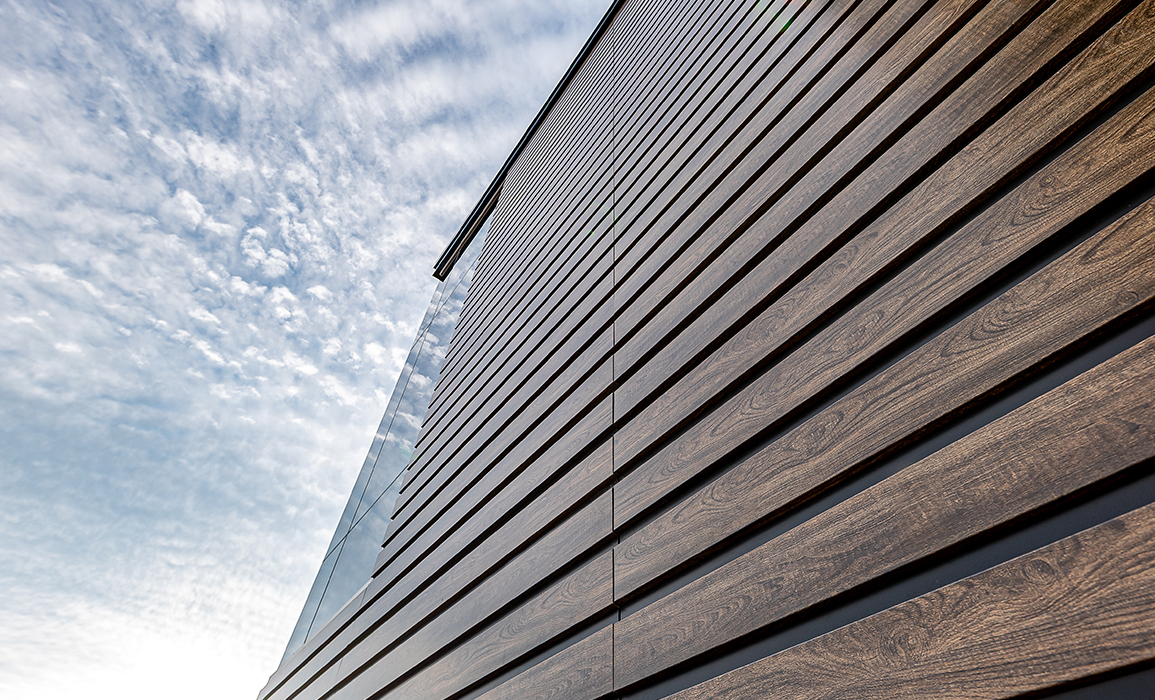 Close up exterior of wood panels on side of building, with blue sky and clouds