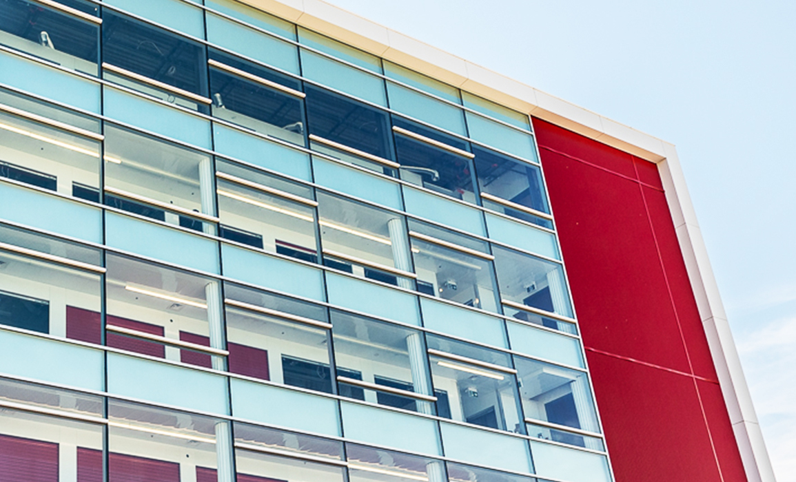 Top corner of a building with lots of windows and a red panel on the side