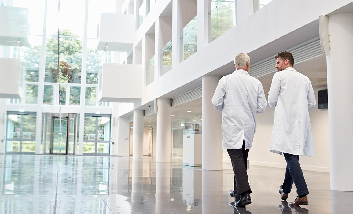 Two men in white lab coats walking in building with tall ceilings and white interior