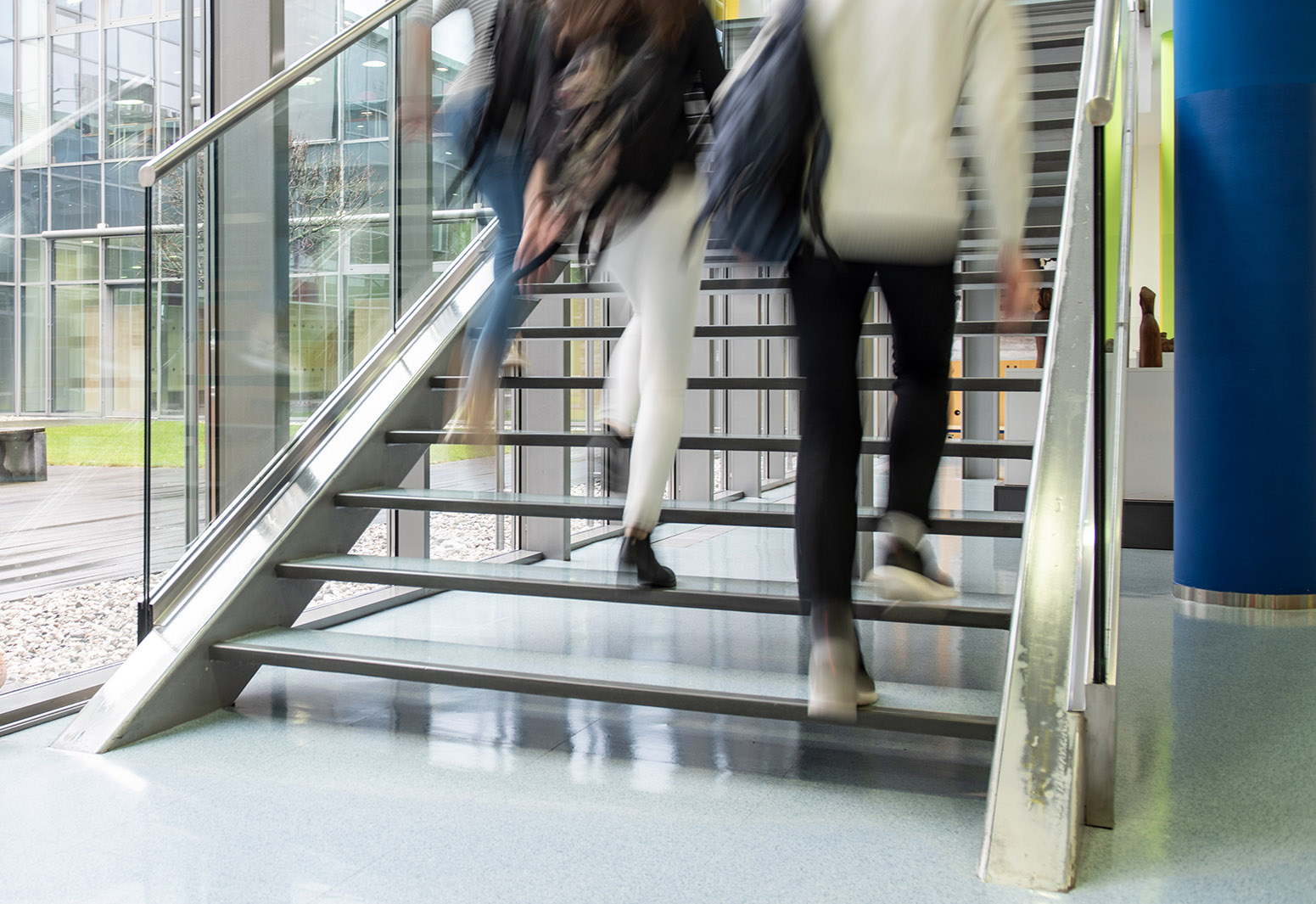 Close up of lower half of people walking up stairs in interior of building with tall windows in background