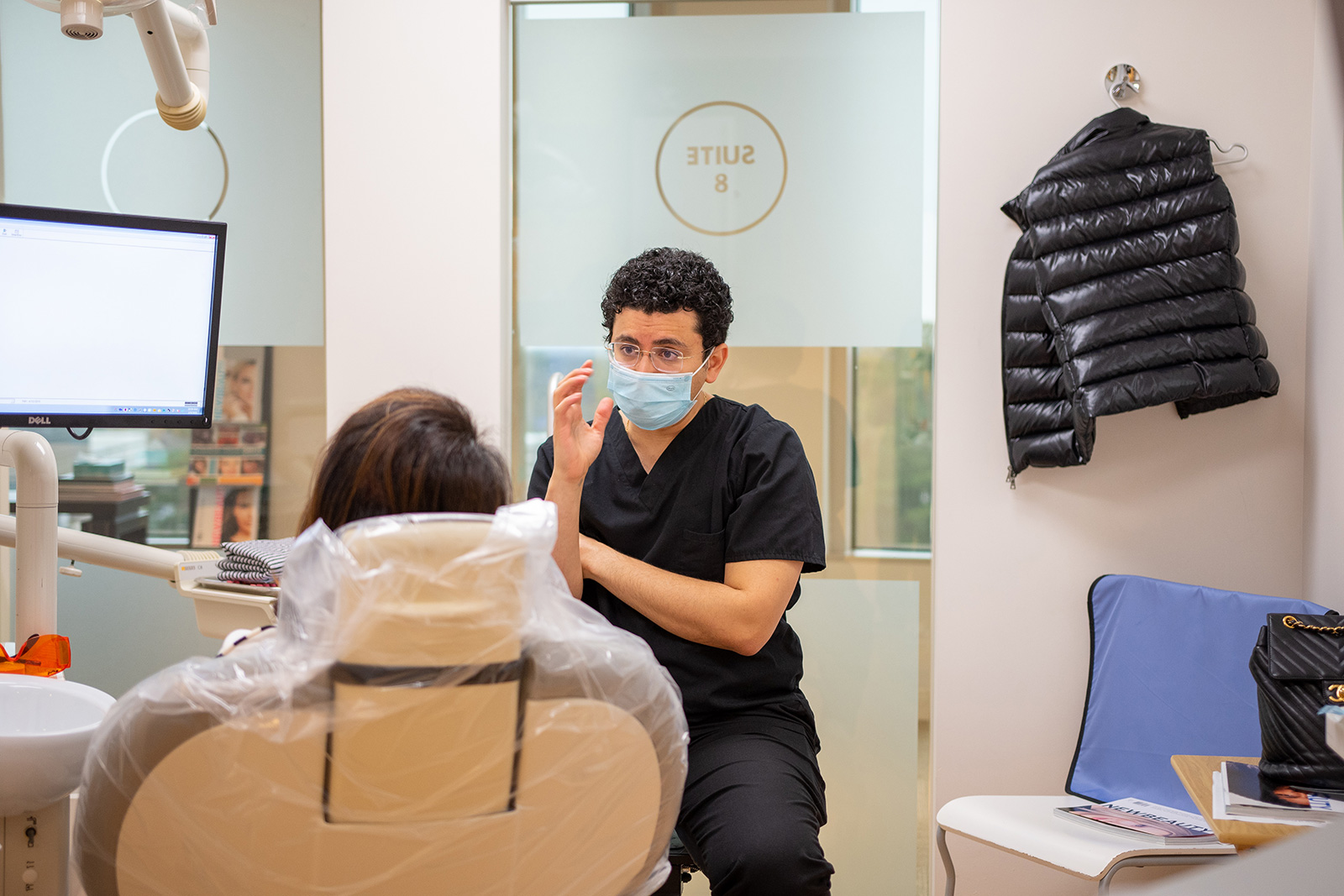 doctor talking to patient on a dental chair