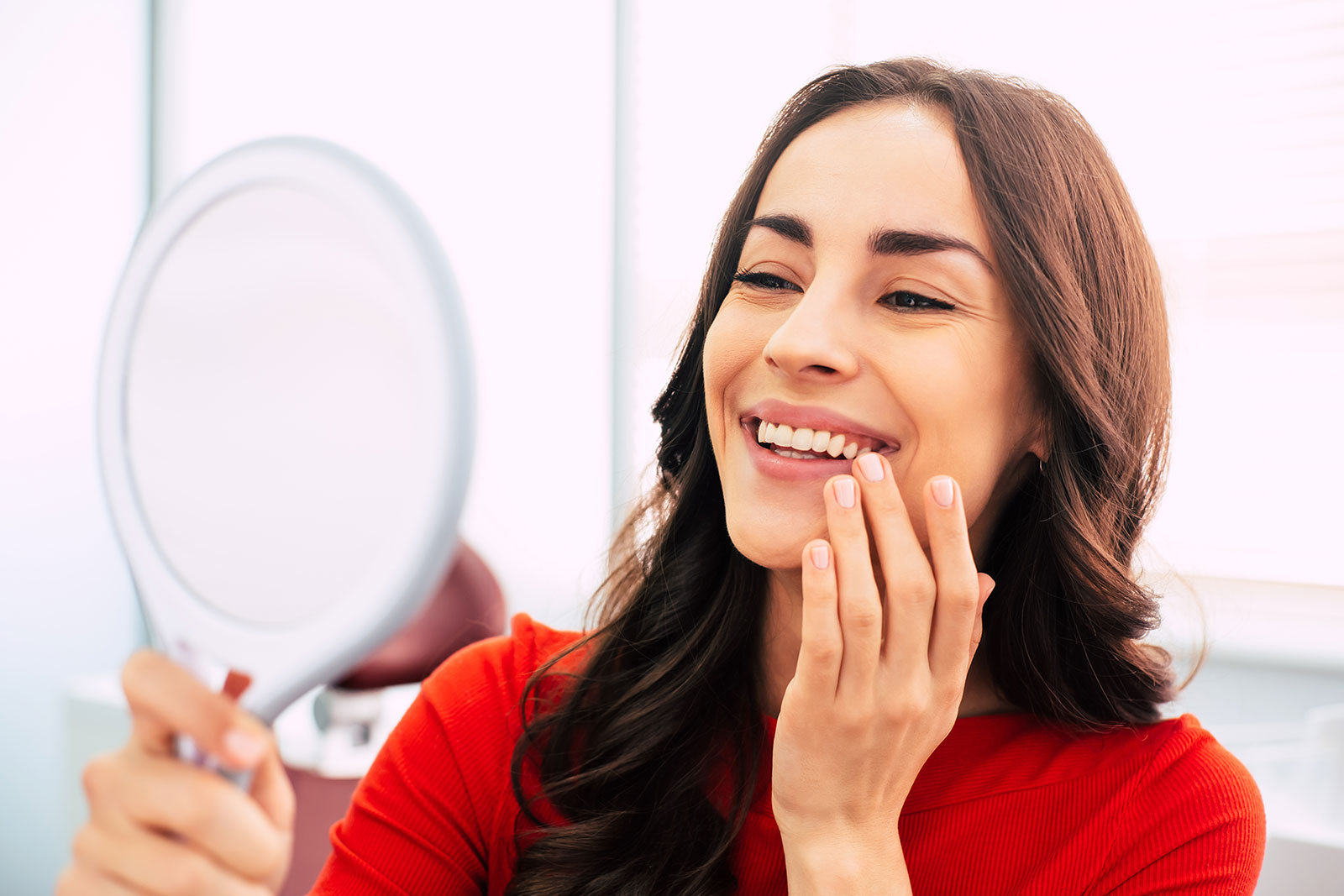 Fabulous woman clothed in red sweater, with curly long hair is holding a mirror for looking through the final work of dental doctor
