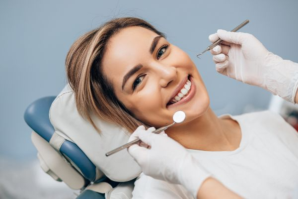 portrait of young caucasian woman with perfect smile in dental office come to treat spoiled teeth look at camera