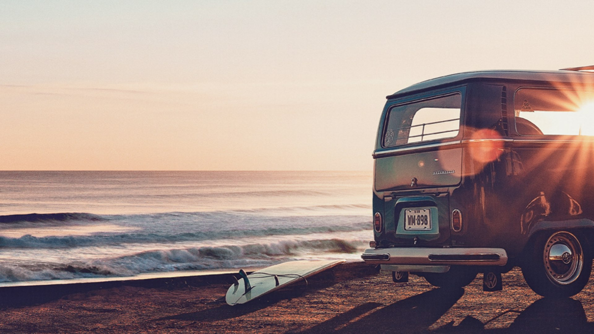 The Works VW Kombi van parked on the beach as the sun sets