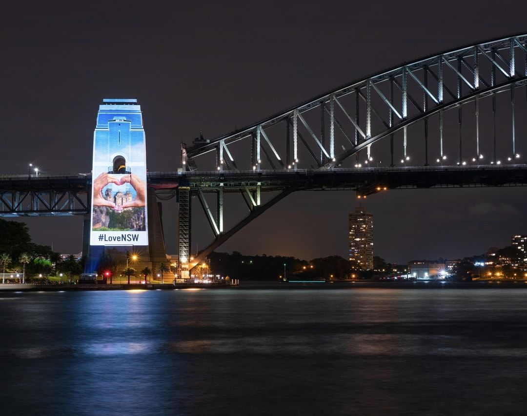 The Sydney Harbour Bridge with a #LoveNSW image projected on to the pylon