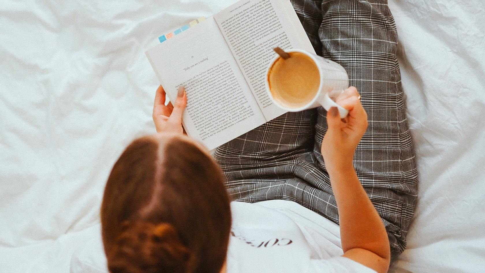 A woman sitting on her bed reading a book with a cup of coffee