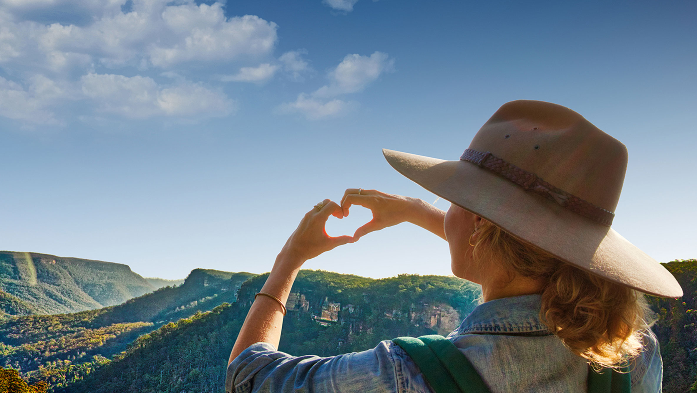 Image of a hiker in the Blue Mountains, making a heart shape with her hands for our Destination NSW #LoveNSW campaign