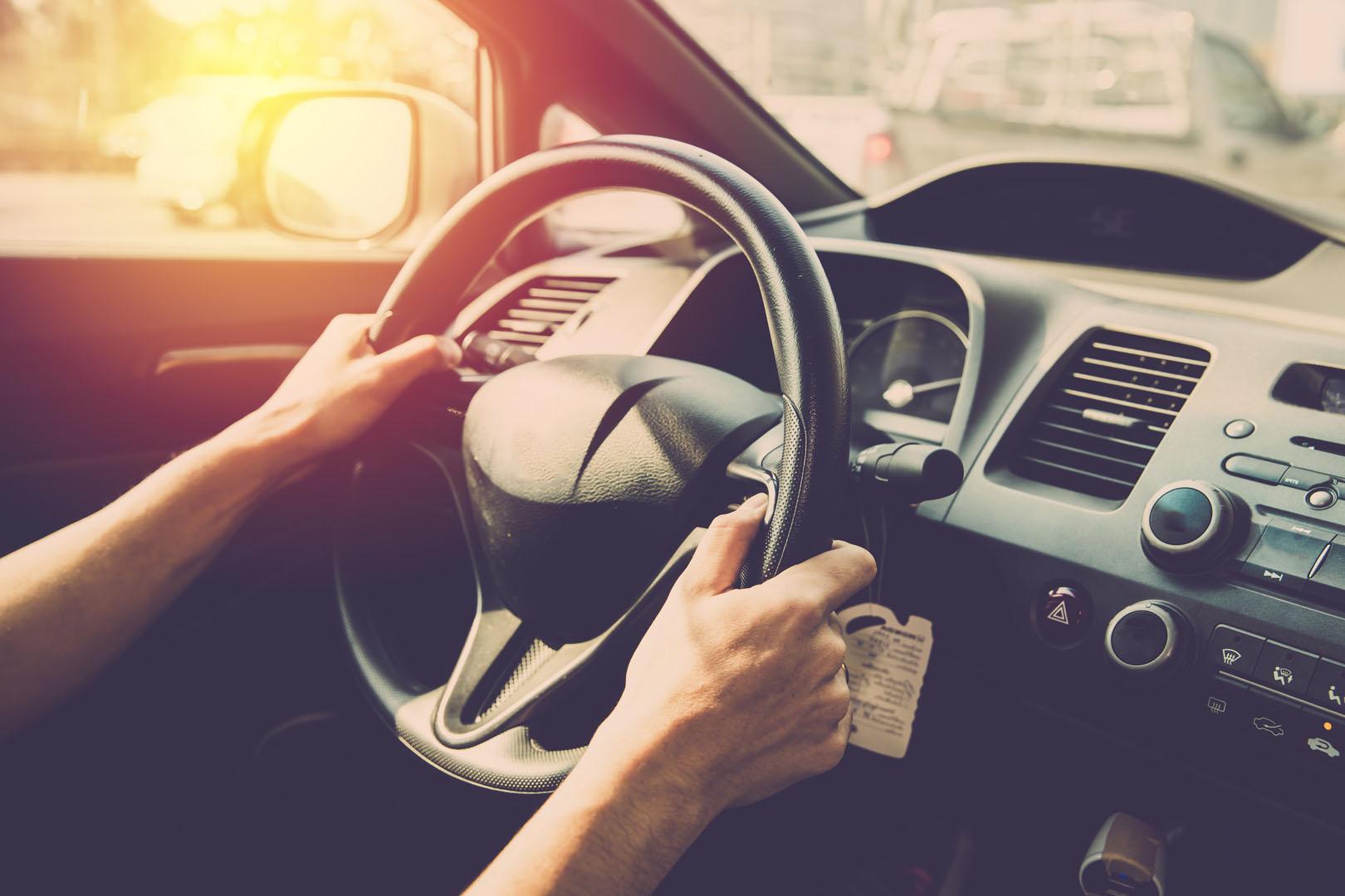 Bilde av sjåfør som holder i bilrattet.