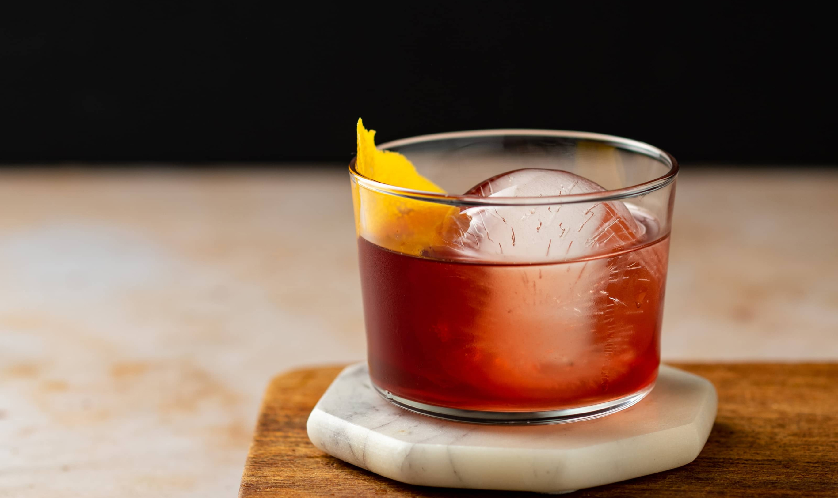 A blueberry negroni against a black back drop
