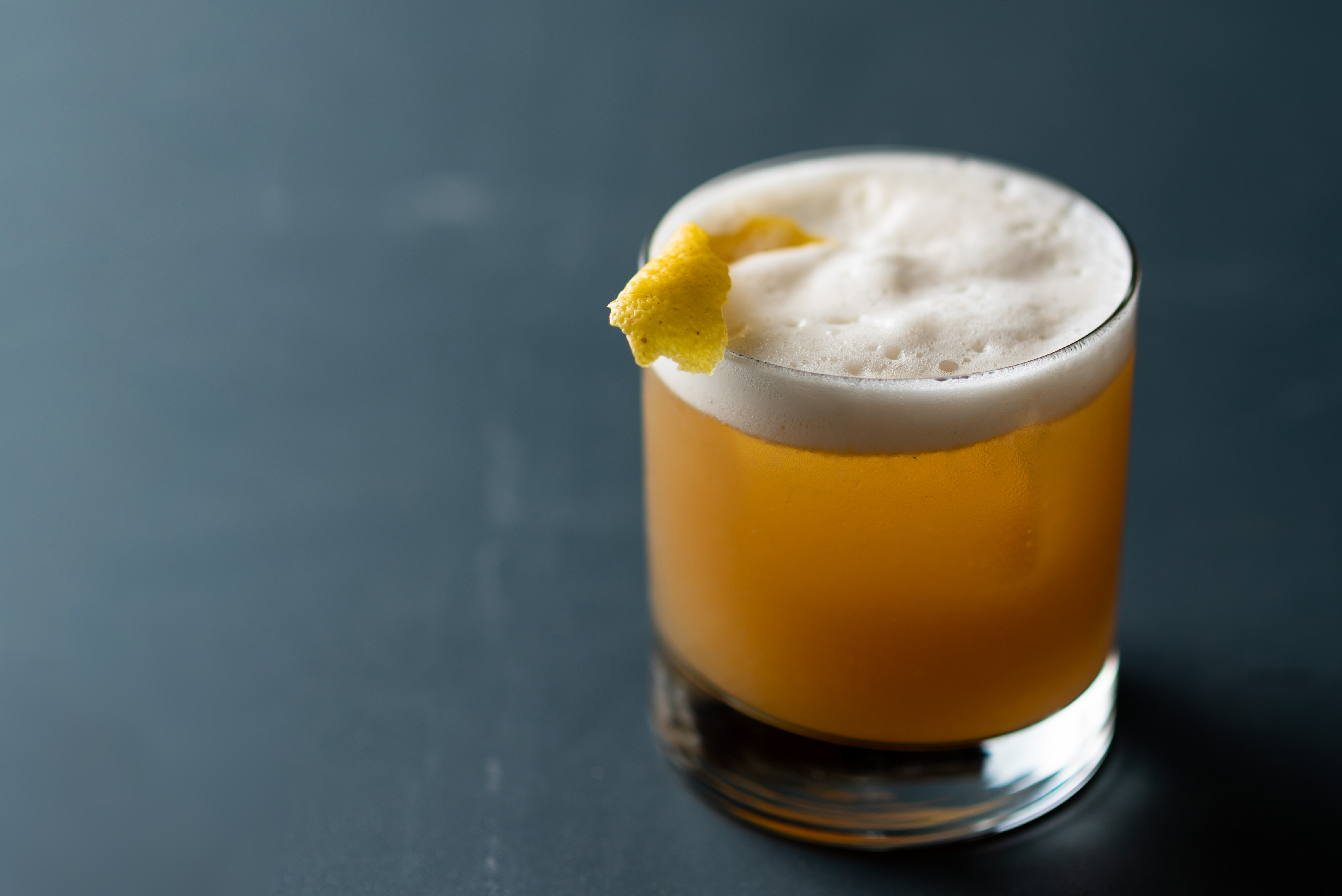 A short tumbler sits on a dark table. Inside, a frothy whiskey sour complete with lemon wedge is ready for drinking.