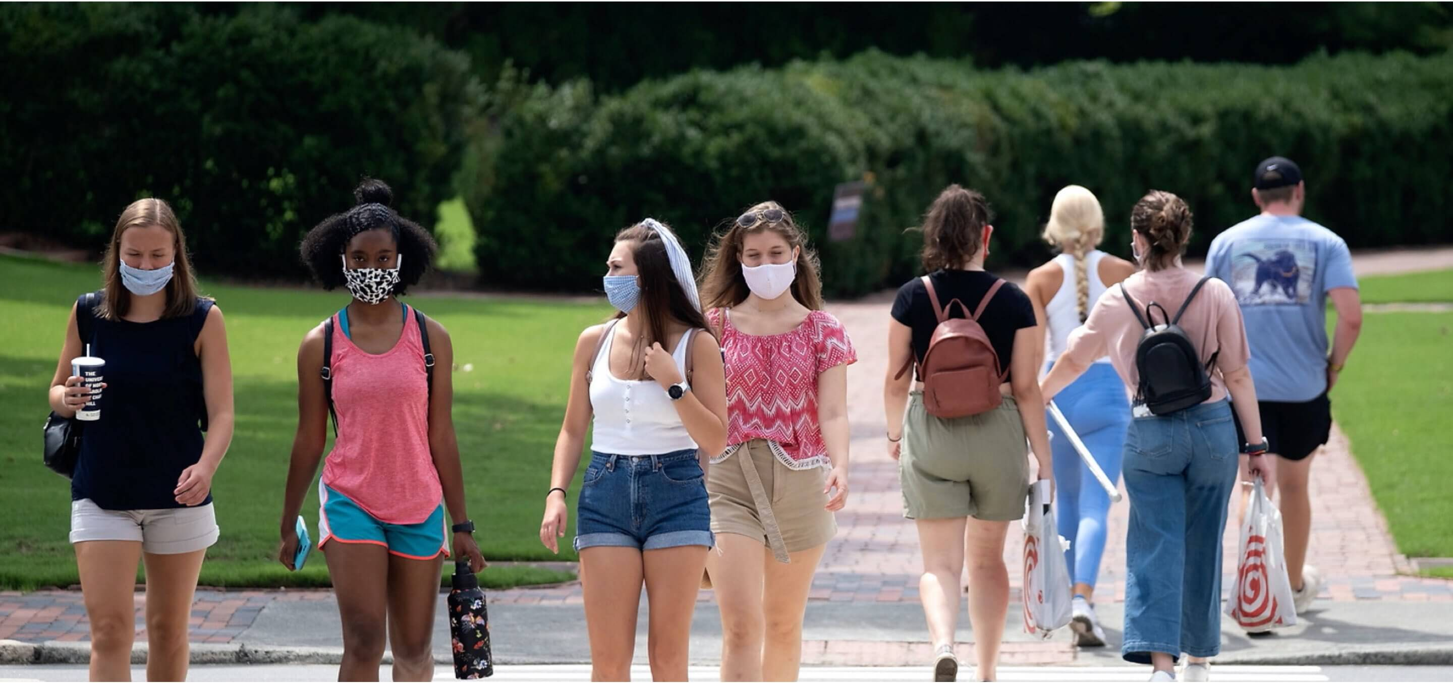 Students walking in groups wearing masks