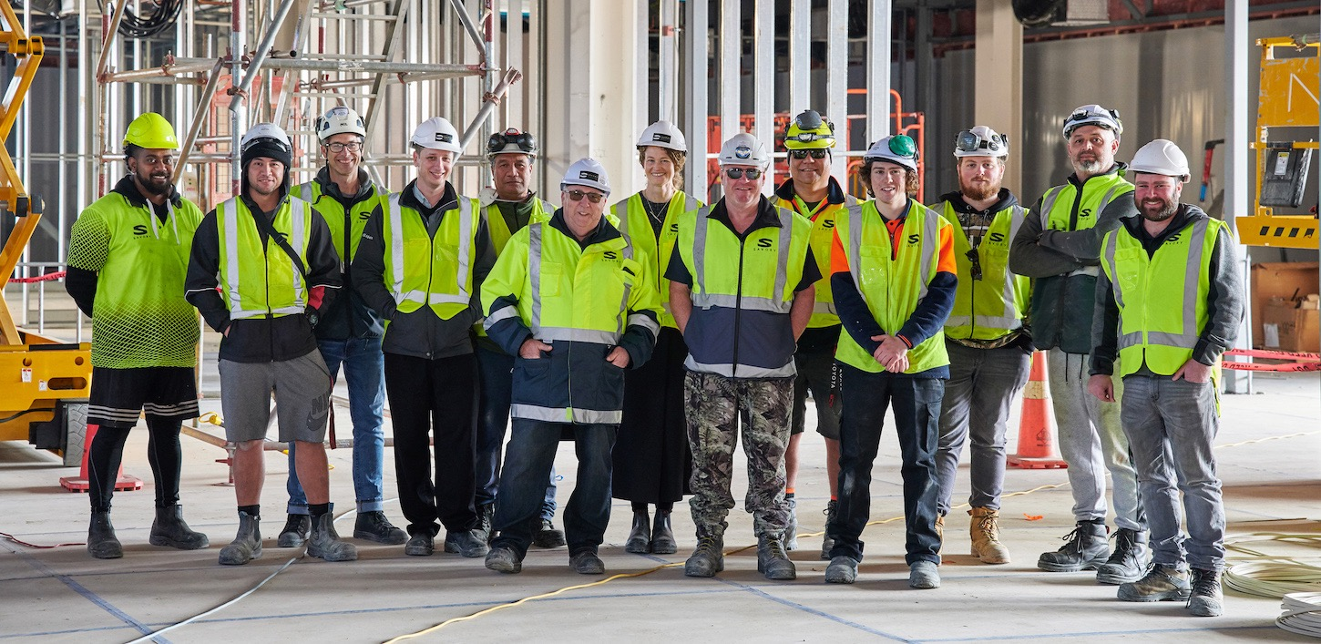 large team of workers standing for a photo. Savory Construction Auckland.