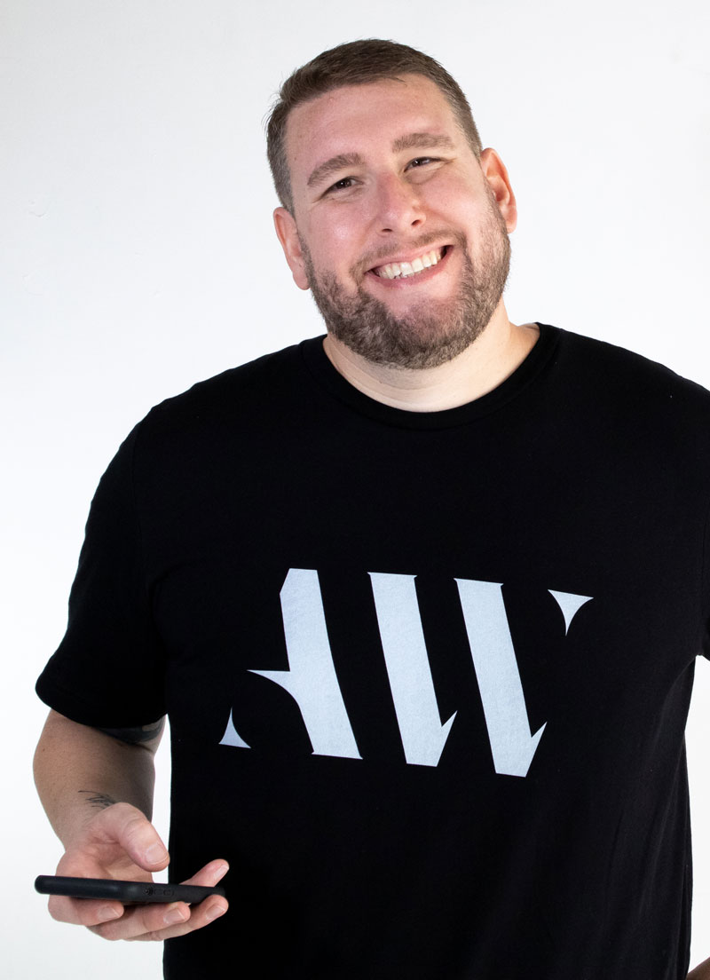 Adam Weitz Smiling with Logo Shirt and Phone