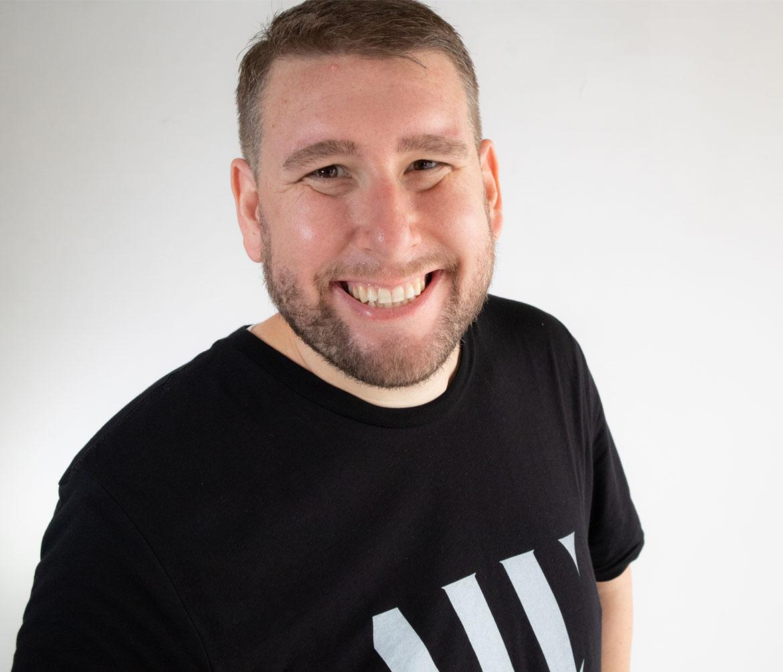 Adam Weitz Profile Smiling with Logo Shirt