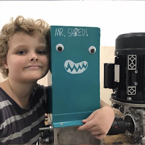 kid hugging a Precious Plastic shredder