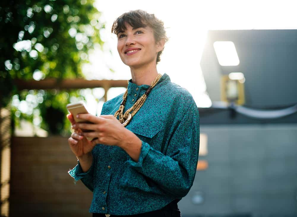 Woman smiling in the sun, planning her next social media post as an affiliate for 3Dsellers eCommerce Selling Tools