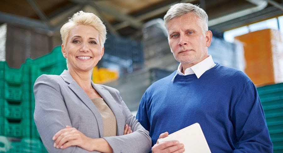 woman and man logistics managers in warehouse