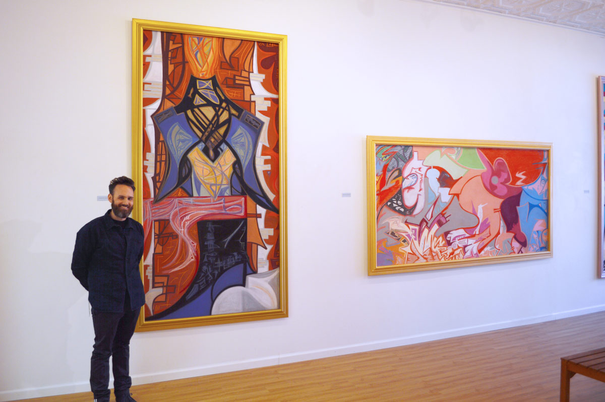 Ian Roche standing with his artwork in gallery