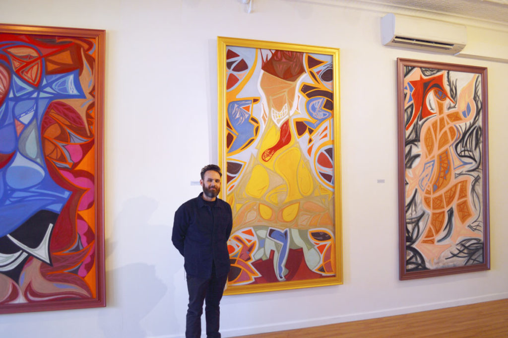 Ian James Roche with paintings in gallery