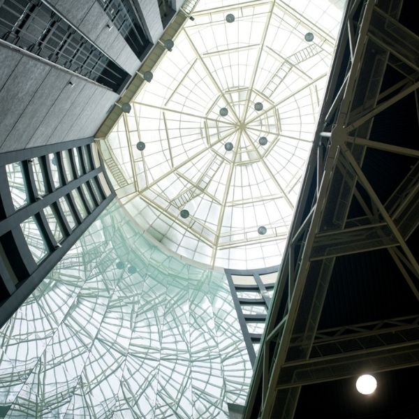 A shot of a building with a glass roof and impressive architecture.