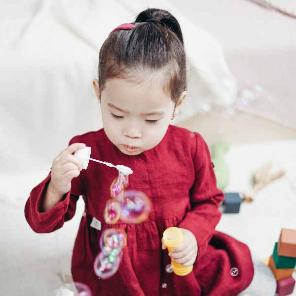 a little girl blowing bubbles