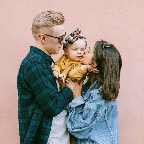 a father and mother kissing their baby girl