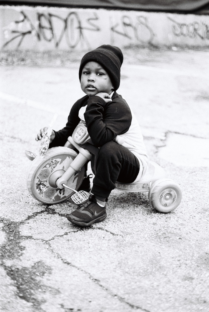 Young black boy sitting out side on his big wheel